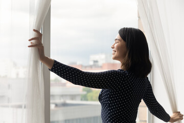 Overjoyed millennial Asian girl open curtains at home meet welcome new sunny early morning in own...