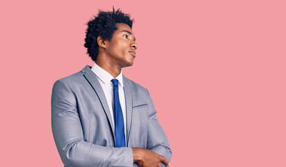 Handsome african american man with afro hair wearing business jacket looking to the side with arms crossed convinced and confident