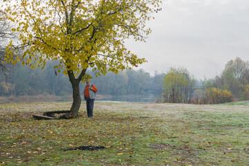 lonely senior tourist standing  under autumnal tree at at Vorskla riverside in ukraine