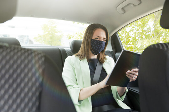 A girl in business clothes is sitting in the back seat of a car with a protective mask on her face and holding a tablet. Work on the way to the office