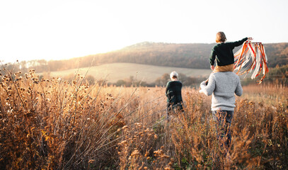Rear view of family with small daughter on a walk in autumn nature.
