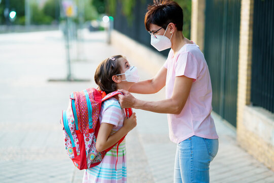 Mother preparing her little girl for the return to school wearing a mask.