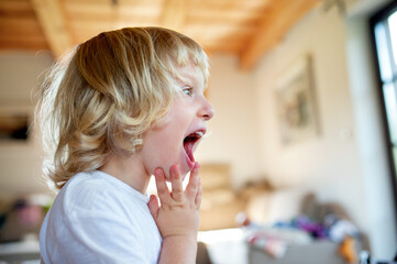 Portrait of small boy with open mouth indoor at home.