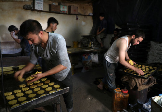 Afghan men prepare cookies at a small traditional factory ahead of the Eid al-Adha, amid the spread of the coronavirus disease (COVID-19), in Kabul