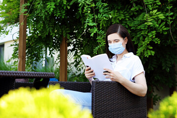A woman in a mask is reading a book while sitting in a cafe. A lonely woman reads a book maintaining a social distance.
