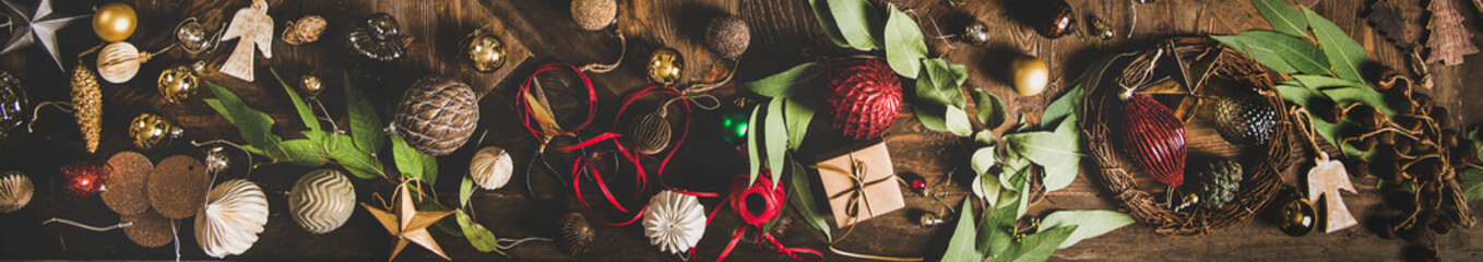 Christmas, New Year holiday background, texture, wallpaper. Flat-lay of decorative objects, fur tree toys, garland, ropes, candles, glass balls, wreaths over rustic wooden background, wide composition
