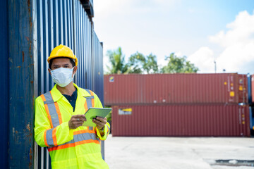 Container worker wearing protective mask to Protect Against Covid-19 working and holding digital...