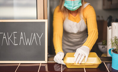 Young woman preparing takeaway food inside restaurant during Coronavirus outbreak time - Worker...