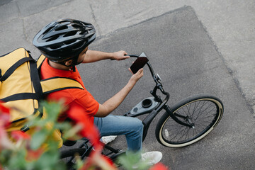 Bicycle courier in protective helmet with delivery backpack sits on bicycle and looks at phone and uses online map on street