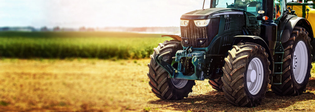 agricultural machinery farm equipment - tractor standing on the field. banner copy space