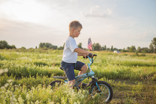 Boy riding his bicycle in a 4th of July on the wind at the green field. Patriotic family celebrates Constitution and Patriot Day.