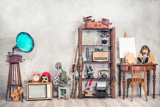 Collection of antique media devices, writers tools, gramophone, film projector, old Teddy Bear toy with canvas blank on easel, travel bag front concrete wall background. Vintage style filtered photo