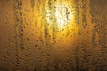 Drops of water on a glass window at dawn as an abstract background.