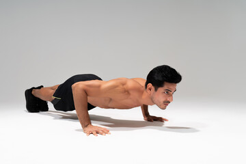 Handsome Man Exercising Against Gray Background
