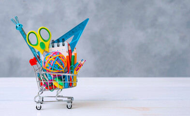 Multi-colored school supplies in a shopping cart on a gray background with copy space for text.