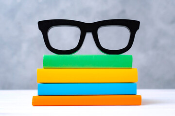 stack of colorful books with glasses on a white wooden table against a gray wall. The concept of going back to school, reading, library, literature, study, education