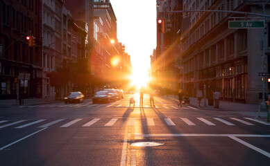 People standing in the middle of the intersection at 23rd Street in New York City taking pictures of the summer sunset