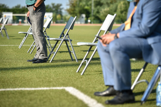 Chairs on the turf of a soccer field maintaining the social distance imposed by corona virus restrictions during an event