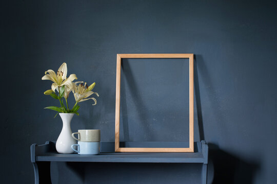 flowers in vase and wooden frame on background dark wall