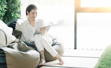 Asian woman usgin smart tablet at home