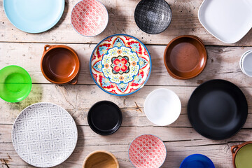 Set of different empty bowls and plates on wooden table