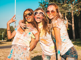 Three happy beautiful girls making party at Holi colors festival in summer time.Young smiling women...