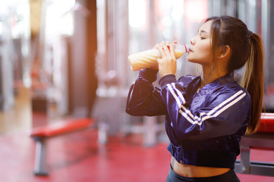 Young asian woman drinking protein shake from bottle after workout exercise for muscle at fitness gym healthy.