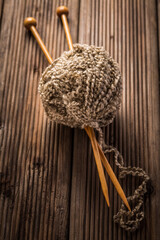 Ball of wool with knitting needles on wooden background