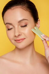 portrait of beautiful naked woman with closed eyes facial jade gua sha isolated on yellow