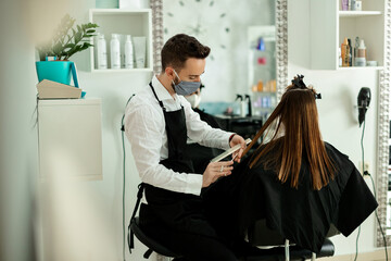 Young hairstylist with protective face mask cutting woman's hair at the salon.