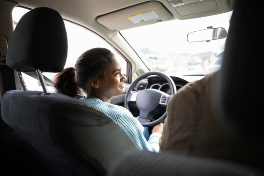 Smiling teenage girl learning to drive car