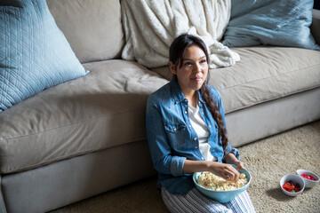 Smiling teen girl eating popcorn and watching TV on living room floor