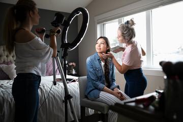Teenage girls vlogging, applying makeup in bedroom