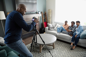 Father with digital camera on tripod photographing family on sofa