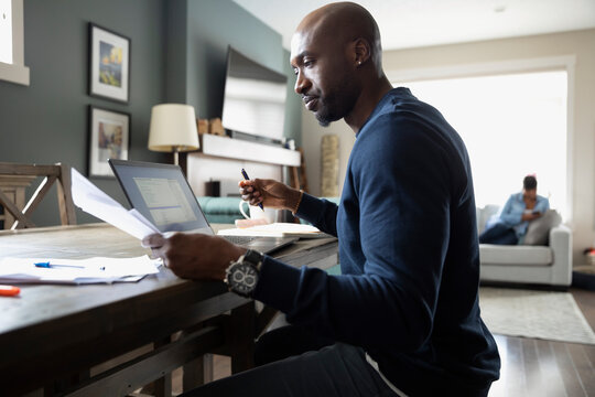 Focused man working from home at laptop