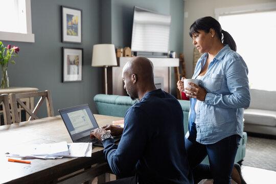 Couple paying bills at laptop