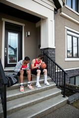 Teenage boys in basketball uniforms talking on front stoop