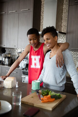 Affectionate son in basketball uniform hugging mother in kitchen
