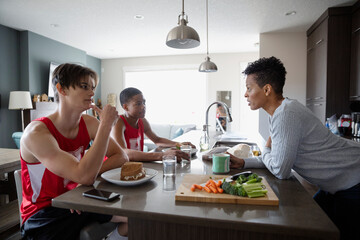 Mother making lunch for teenage son and friend in basketball uniforms