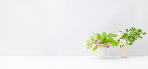 Home interior with decor elements. Pink small flowers and green leaves in a vase on a light...