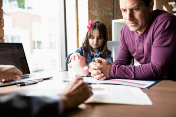 Father and daughter with piggy bank meeting with financial advisor