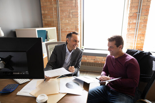 Smiling financial advisor talking with man in office