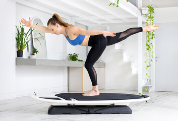 Young woman doing a surfing yoga runner pose