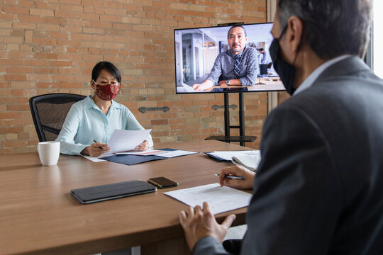 Business people in face masks video conferencing in office meeting