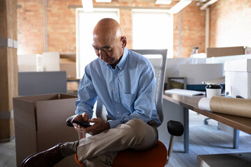 Businessman using smart phone in new open plan office