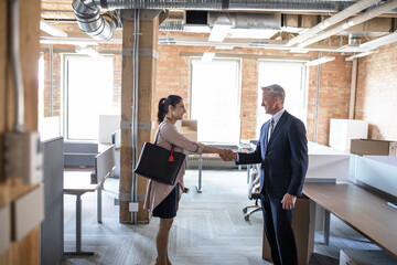 Business people shaking hands in new open plan office