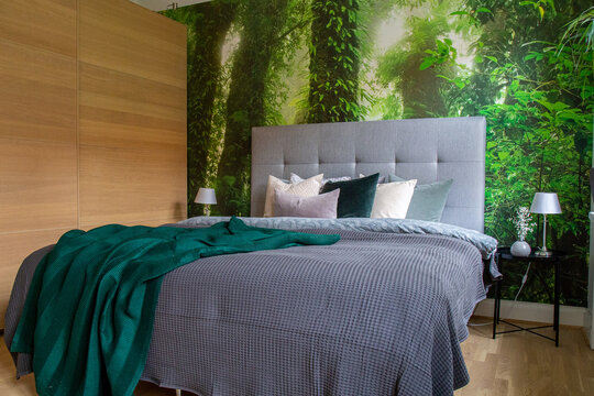 Bed with grey bedding, green blanket against a djungle photo wallpaper