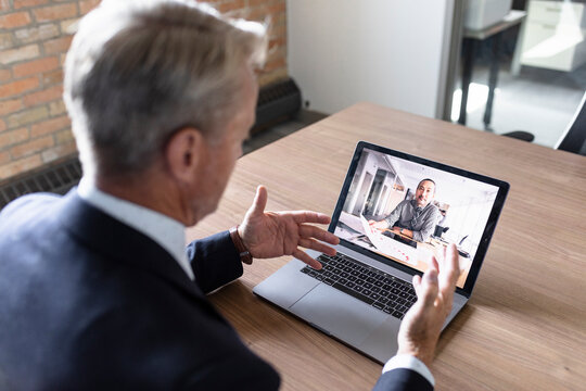 Businessmen video conferencing by laptop in office