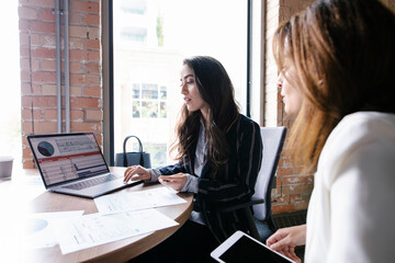 Businesswomen planning at laptop in conference room