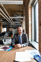 Portrait confident businessman with smart phone in office